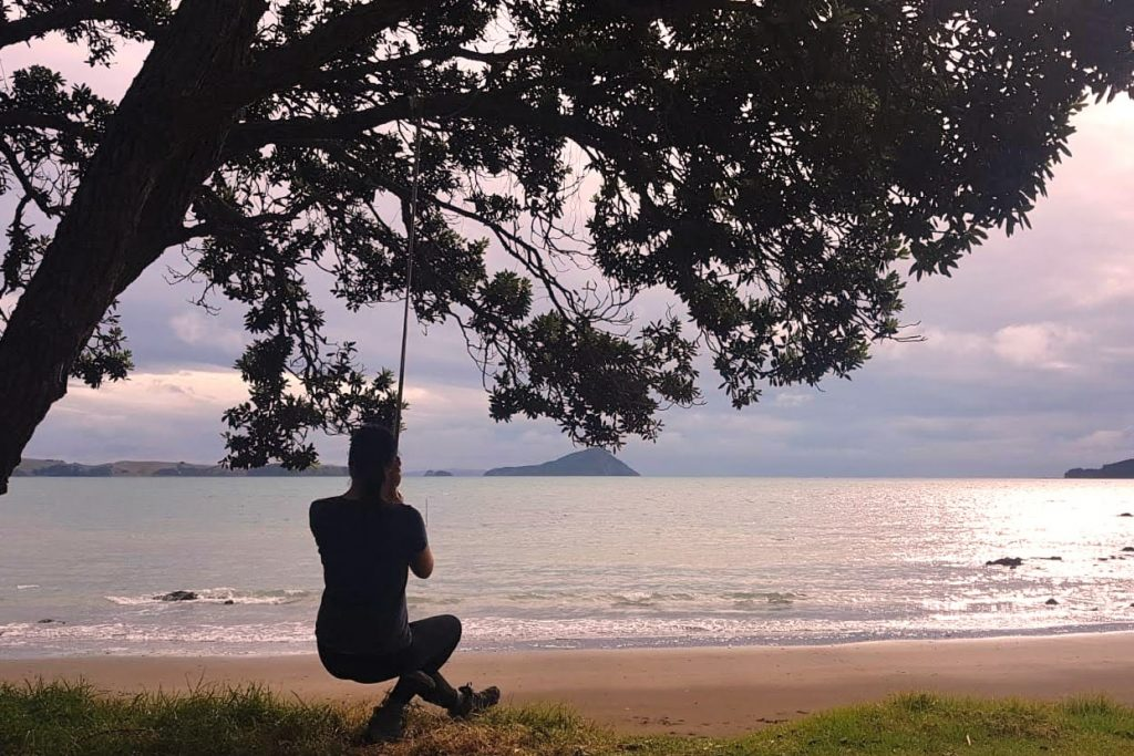On a swing at the beach of Long Bay, Coromandel Town, New Zealand