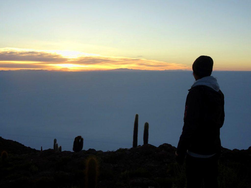 Silhouette in front of sunrise in the Salar de Uyuni salt flat, Bolivia