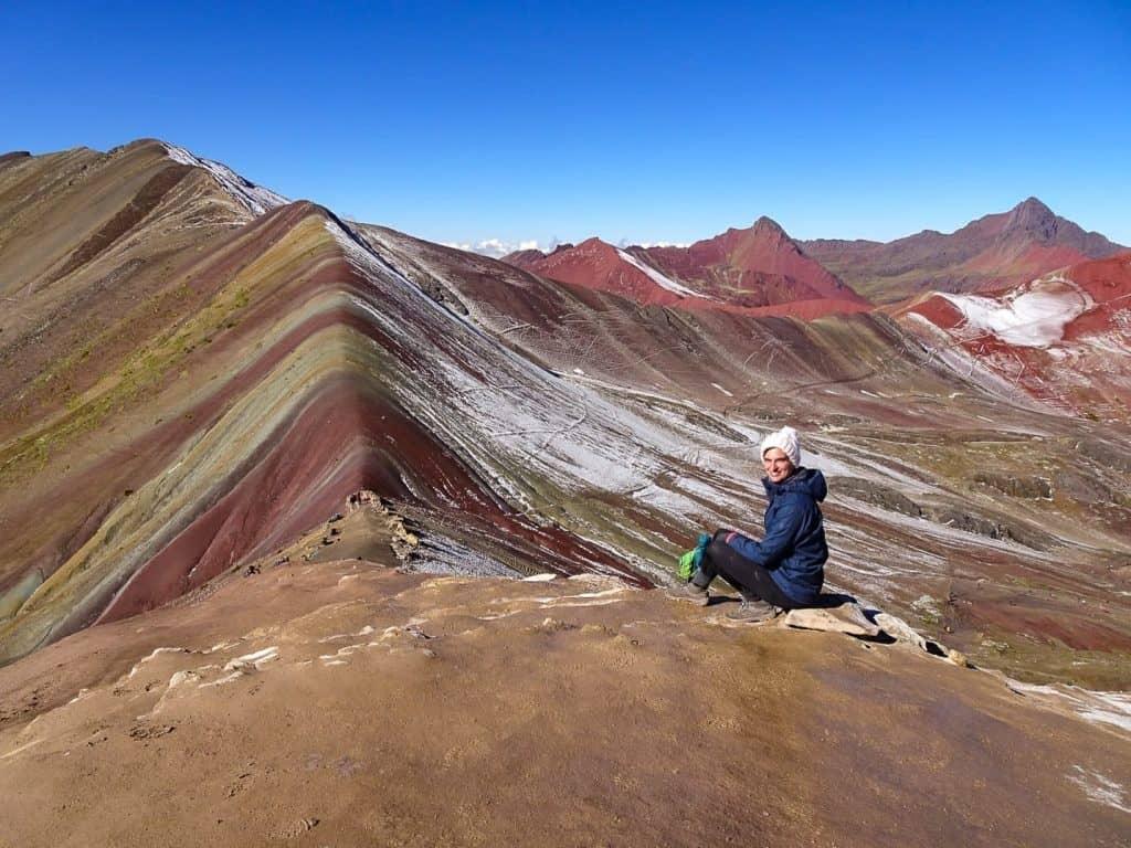 Woman sitting before panorama of multi-coloured mountains, Rainbow Mountain, Peru